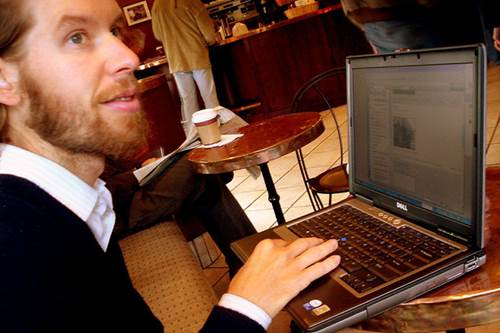 Man Working on a Laptop in a Cafe